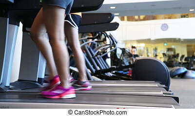 treadmill - Low camera side view of two ladies on treadmill.