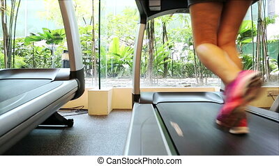 treadmill - Back view of a lady running on treadmill