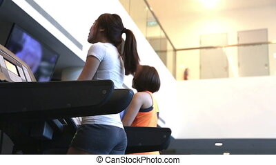 treadmill - Low camera view of two asian ladies on treadmill...
