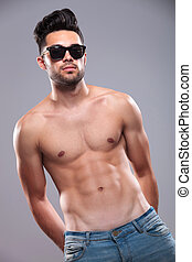 topless man holds hands in back pockets - topless young man...