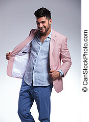 casual man takes off jacket and smiles - young casual man...