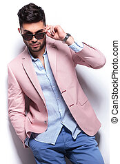casual man with hand in pocket takes off sunglasses - young...
