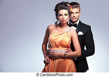 fashion couple with man behind woman
