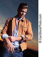 casual man pulls up his sleeve at sunset - casual young man...