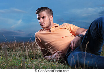 casual man laying in the grass and looking away - young...