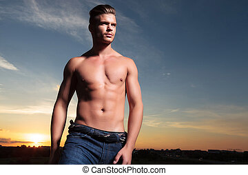 topless man looks away during sunset - young topless man...