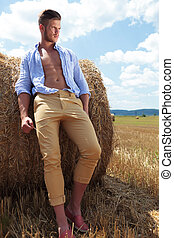 casual man outdoor leans on haystack and looks away - full...
