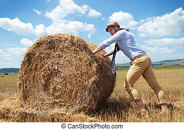 casual man outdoor pushes a haystack - full length photo of...