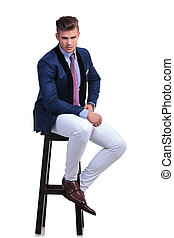 seated young business man with hand on his hip - full length...