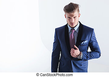 young business man with hand on jacket lapel - young...