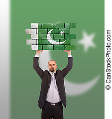 Businessman holding a large piece of a brick wall, flag of...