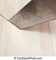 wooden board is cut with hacksaw close up
