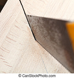 wooden plank is cut with hacksaw close up