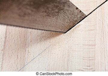 wood board is cut with hacksaw close up