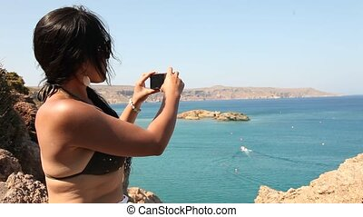 Woman taking Picture - young woman taking a picture at Beach...