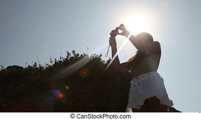 Woman taking photo - young woman taking a picture at Beach...
