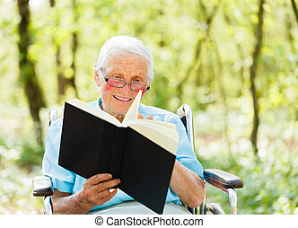 Reading Senior Lady - Kind elderly lady in wheelchair with...