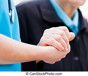 Helping Elderly - Caring nurse or doctor holding elderly...