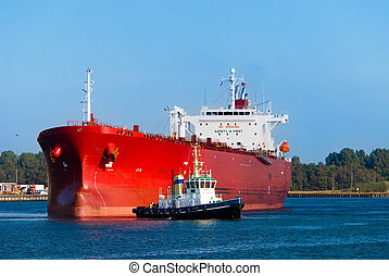 oil tanker and a tugboat - A huge red oil tanker and a...