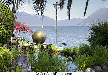 Plants and lake with snow-capped mountain with sailing boat