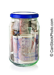 British Pounds banknotes in a glass jar over white...