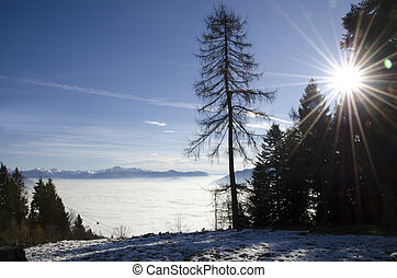 Sea of fog over an alpine lake with snow-capped mountain and...