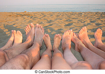 many barefoot of a family on the shore of the sea on the...