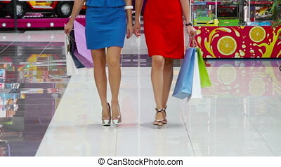 Excited shopaholics - Tilt up of two lovely ladies enjoying...