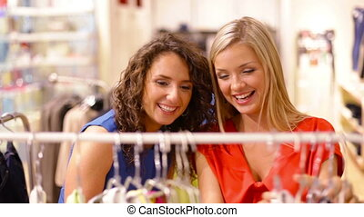 By racks - Young women choosing clothes hanging on the racks