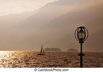 Lake with sailing boat and island with a lighthouse - Alpine...