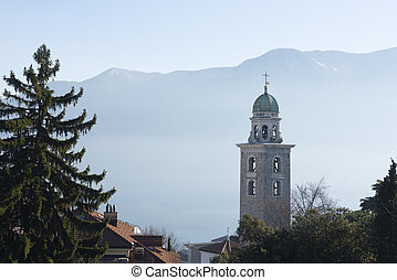 Church tower and trees with mountain