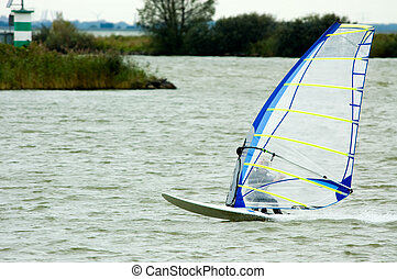 windsurfer going fast on a lake