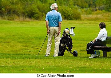 senior couple playing golf - senior couple  playing golf