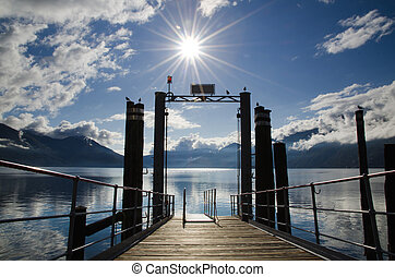 Port in backlight - Harbor on an alpine lake with mountains...