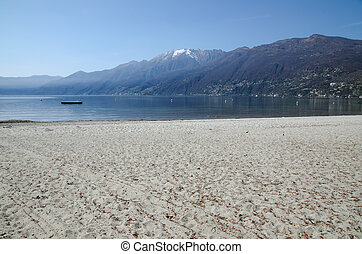 Beach with snow-capped mountains - Sand beach on an alpine...