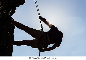 Silhouetted Man Climbing Rock - Low angle view of...