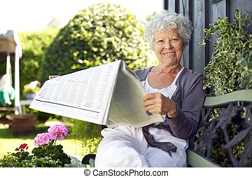 Senior woman reading newspaper in backyard garden