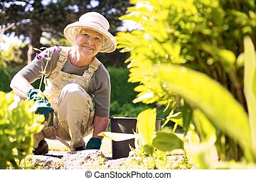 Happy elder woman working in her garden - Happy elder woman...