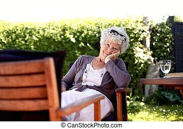 Senior woman relaxing in backyard garden