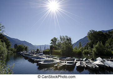 Port in backlight - Small harbor with sunbeam and mountain