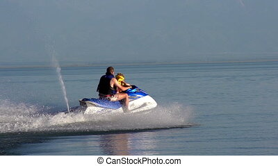 Water Activities - The man rolls the small son on a jet ski....