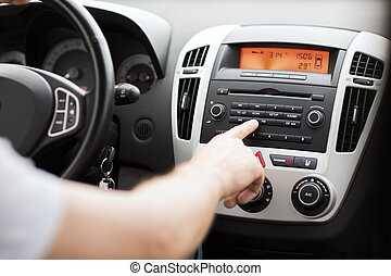 man using car audio stereo system - transportation and...