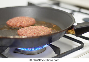cooking meat on a stove