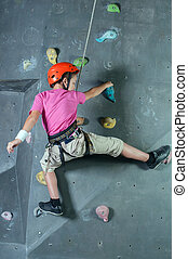 Climbing the wall - Child climbing on a wall in a climbing...