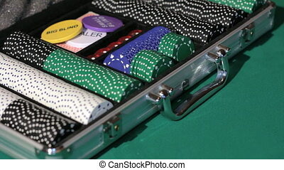 Hands close the aluminium suitcase with poker set.