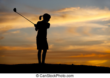 Silhouetted girl swings club. - A young girl in silhouette...