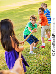 Kids Playing Tug of War On Grass - Group of Kids Playing Tug...