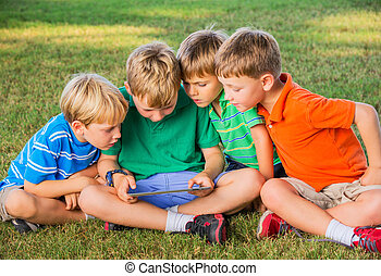Kids using tablet computer - Group of Kids Sitting on grass...