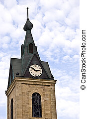 Clock tower on the blue cloudy sky background