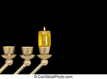Close up of a lit oil menorah for the Jewish holiday. Small...